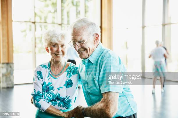 Laughing senior couple dancing together in ballroom