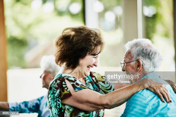 laughing senior couple dancing together in community center - green dress stock pictures, royalty-free photos & images