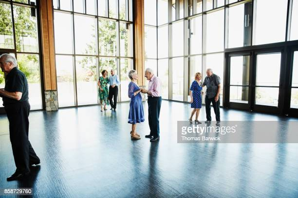 Laughing senior couple holding hands after dancing in community center