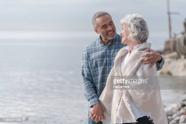 laughing senior couple on a beach - life insurance stock pictures, royalty-free photos & images