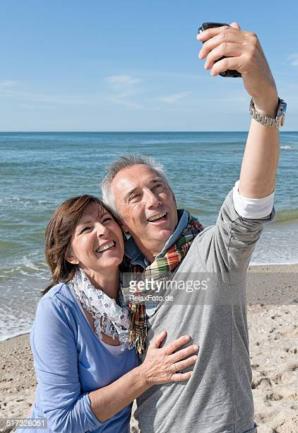 Laughing Senior couple on beach making selfie with mobile