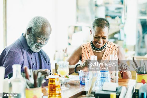 Laughing senior couple sharing lunch in restaurant on summer afternoon