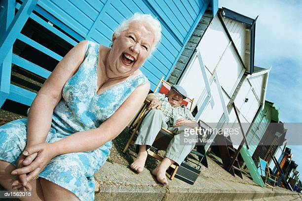 Laughing Senior Couple Sitting in Front of Beach Hut