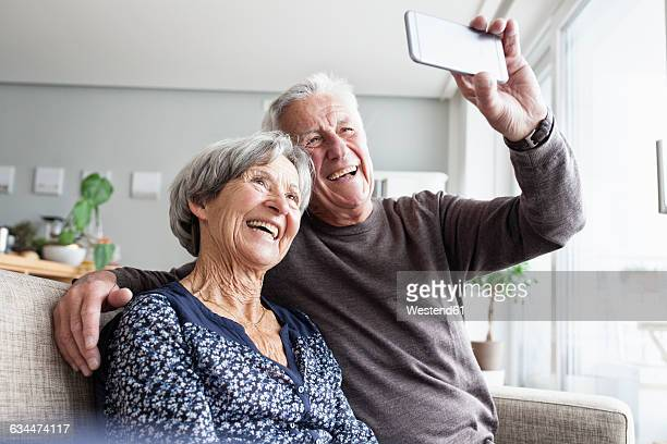 Laughing senior couple sitting on the couch in the living room taking selfie with smartphone