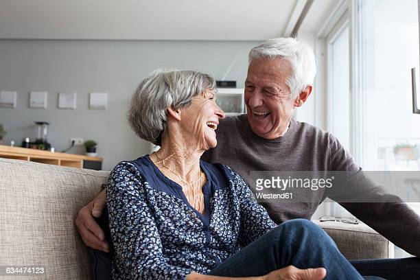 Laughing senior couple sitting together on the couch in the living room