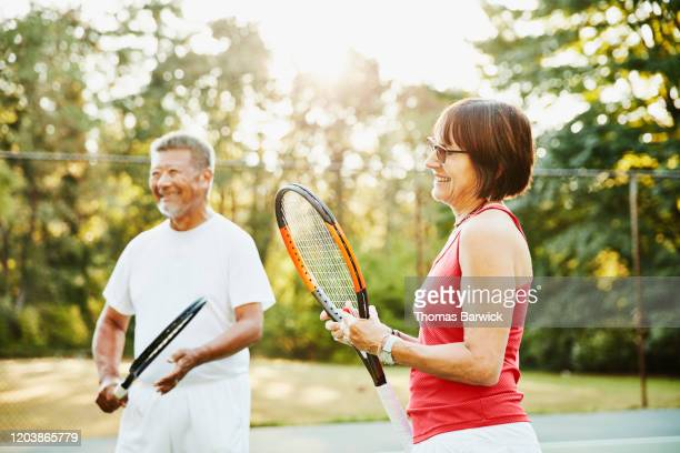 laughing senior friends in discussion at net during early morning tennis match - wellness stock pictures, royalty-free photos & images