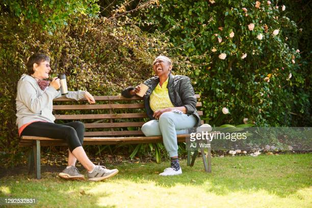 laughing senior friends sitting together on a park bench - bench stock pictures, royalty-free photos & images