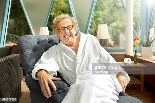 Laughing senior man in bathrobe sitting in armchair