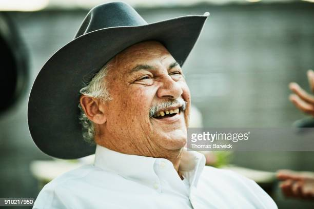 laughing senior man in cowboy hat in discussion with family member during outdoor dinner party - texas independence day stock pictures, royalty-free photos & images
