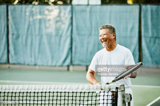 laughing senior man on tennis court before early morning match - disruptaging stock pictures, royalty-free photos & images