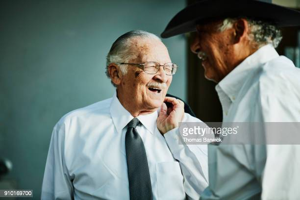 Laughing senior men greeting each other before outdoor family celebration