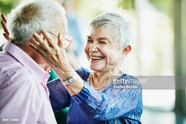 Laughing senior woman embracing partner after dance in community center