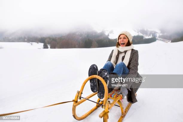 laughing senior woman sitting on sledge in snow-covered landscape - winter sport stock pictures, royalty-free photos & images
