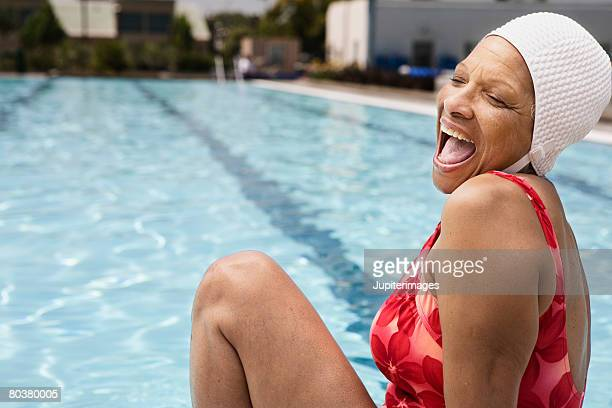 Laughing senior woman swimmer at pool
