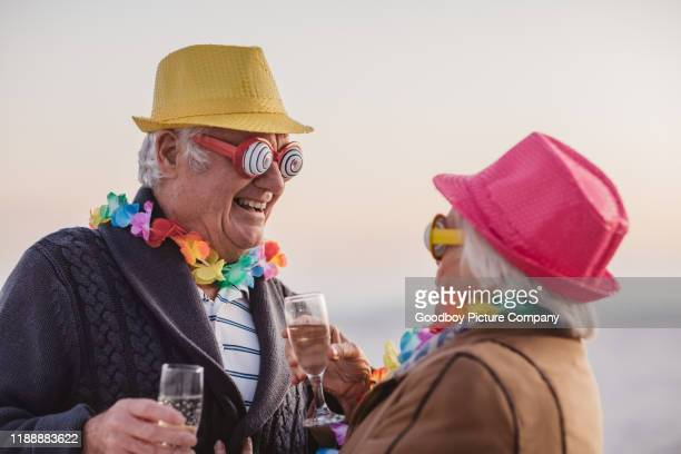 laughing seniors celebrating new year's together at the beach - 70 year old man stock pictures, royalty-free photos & images
