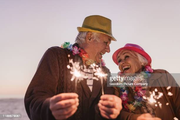 laughing seniors celebrating new year's with sparklers at the beach - 70 year old man stock pictures, royalty-free photos & images