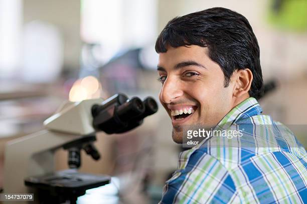 Laughing Student With Microscope In A Laboratory