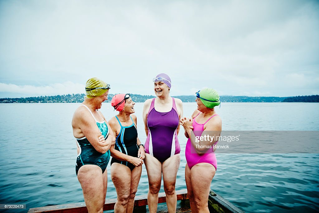 Laughing swimmers preparing for morning swim : Stock Photo