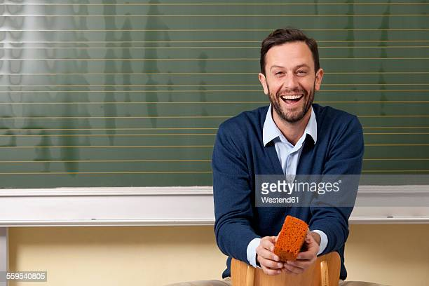 Laughing teacher in classroom at blackboard