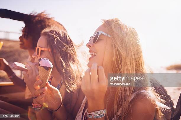 Lachen teen Mädchen isst Eis zusammen am Strand