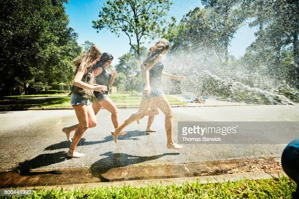 Laughing teen girls running through spray from fire hydrant on summer afternoon