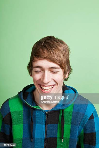 A laughing teenage boy, portrait, studio shot