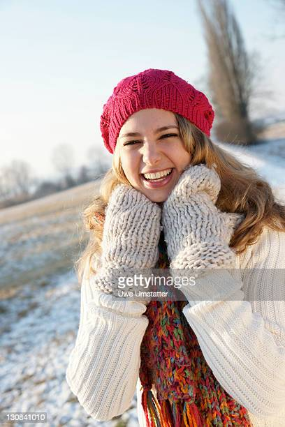 Laughing teenage girl wearing a hat and gloves in a wintery landscape
