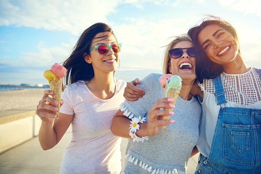 Laughing teenage girls enjoying ice cream cones 1019427352