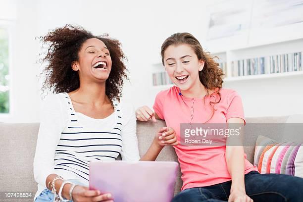 Laughing teenage girls using laptop together