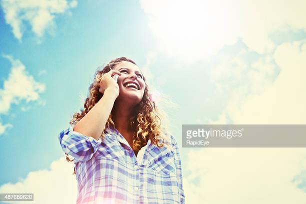 Adolescente riant sur le téléphone en chambre lumineuse de soleil avec lentille flare