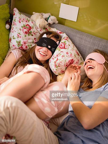 Laughing teens with sleeping masks on a bed in pyjamas