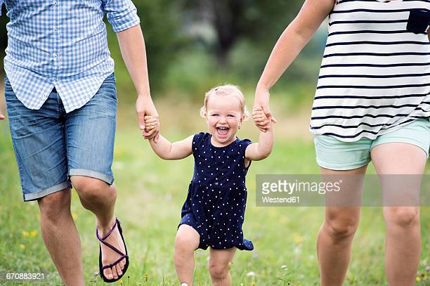 Laughing toddler girl holding hands of parents while running