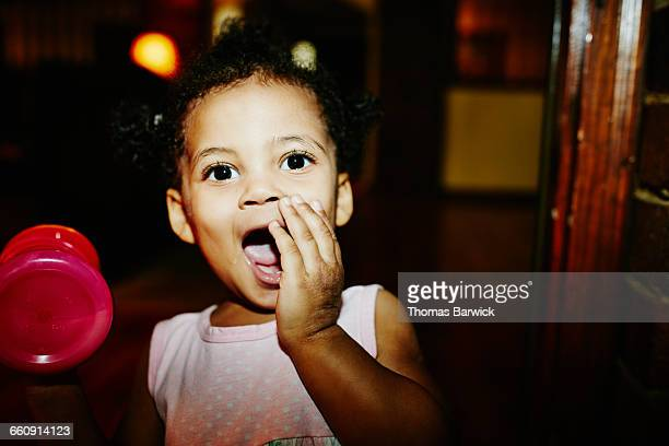 Laughing toddler girl in home during party