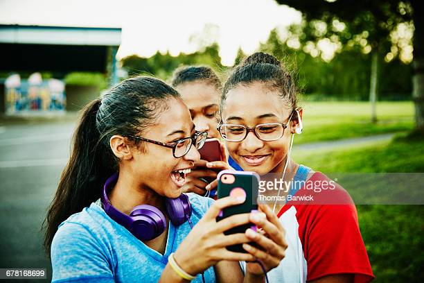 Laughing twin sisters looking at smartphone