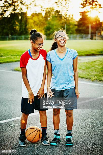 Laughing twin sisters on basketball court