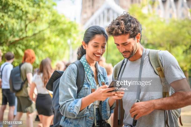 les vacanciers riants vérifiant le téléphone intelligent pour des directions - escapade urbaine photos et images de collection