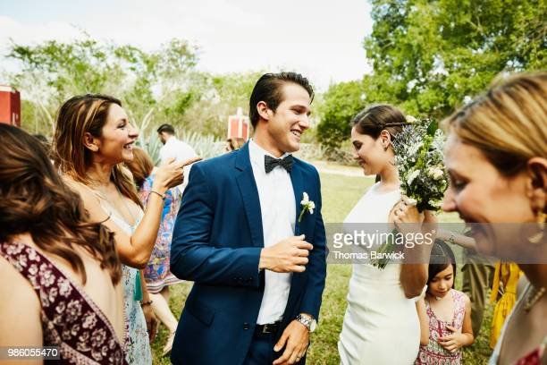 laughing wedding guests hanging out with bride and groom after outdoor ceremony at tropical resort - wedding guest stock pictures, royalty-free photos & images