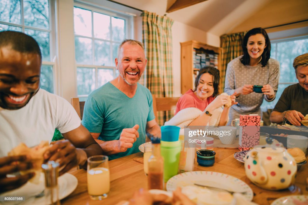 Laughing with Friends at the Breakfast Table : Stock Photo