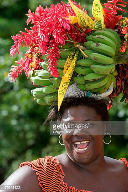 Laughing woman carries fruit on head
