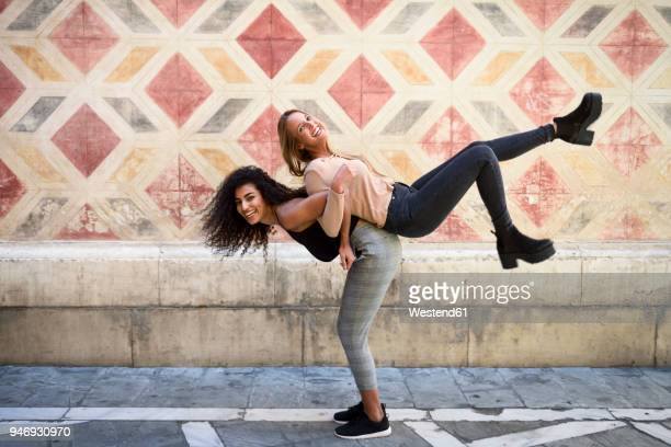 Laughing woman carrying her best friend piggyback