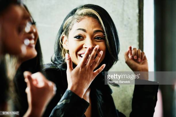 laughing woman covering mouth with hand while sharing meal with friends - hands covering mouth stock pictures, royalty-free photos & images