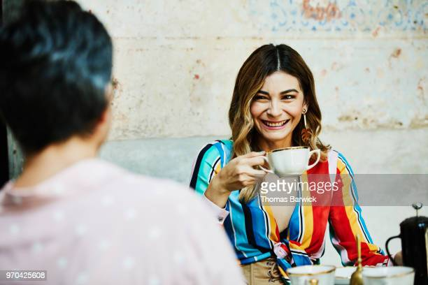 Laughing woman drinking coffee with husband while seated at outdoor cafe