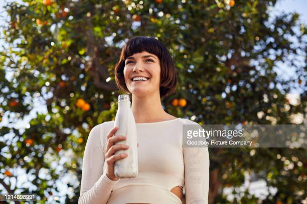 laughing woman drinking water bottle after an outdoor exercise session - reusable stock pictures, royalty-free photos & images