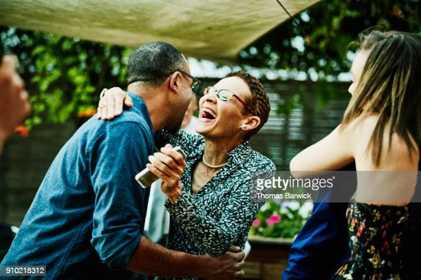 Laughing woman embracing brother inlaw after outdoor family dinner party