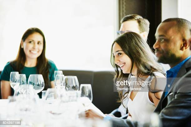 Laughing woman enjoying celebration meal with friends in restaurant