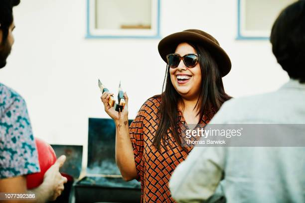 laughing woman grilling food on barbecue during party with friends - funny bbq stock pictures, royalty-free photos & images