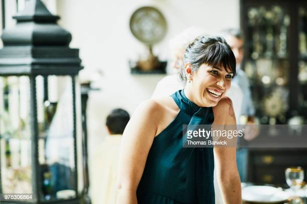 Laughing woman hanging out with family members during celebration dinner