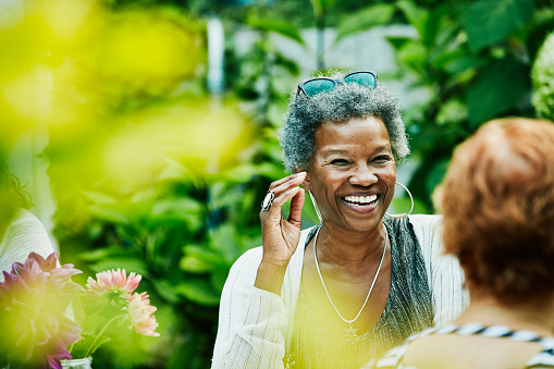 Laughing woman hanging out with friends during backyard dinner party - gettyimageskorea