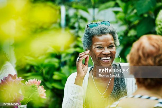 laughing woman hanging out with friends during backyard dinner party - image saisie sur le vif photos et images de collection