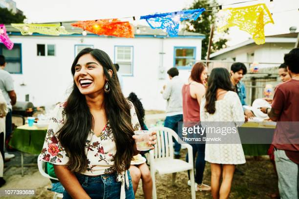 laughing woman hanging out with friends during backyard party - latino américain photos et images de collection